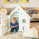 boy playing with dolls house