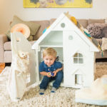 A boy playing with a Doffie doll house