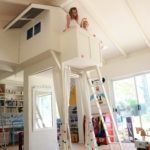 girl playing in playroom underneath indoor cubby house