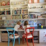 kids playroom with girls sitting in front of bookshelf