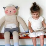 girl sitting next to large doll